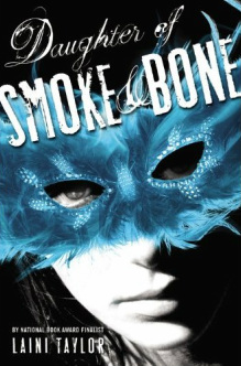 Daughter of Smoke & Bone cover. The cover has a black background and whimsical script with the title. The picture is of a girl, partially hidden in shadow, with a turqoise masquerade mask covering her face. The mask is made of feathers.
